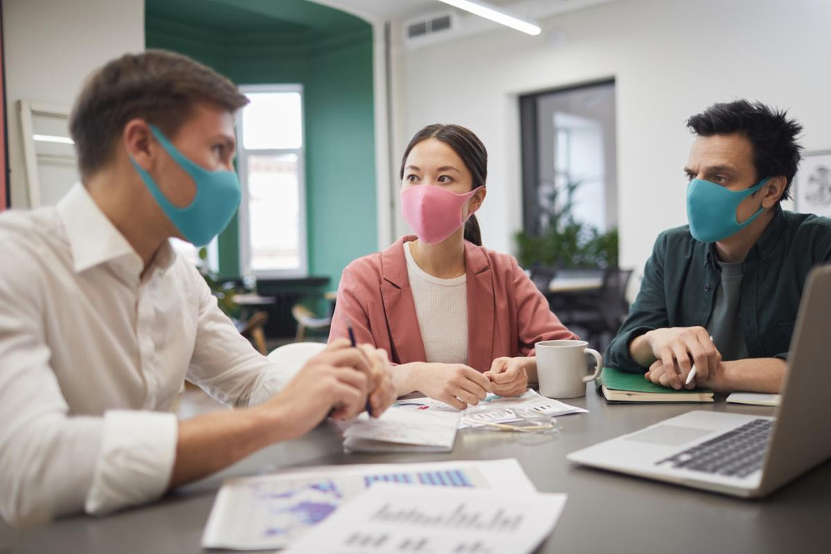 Three people with masks on sitting together at table, contact tracing technology, face mask detection technology