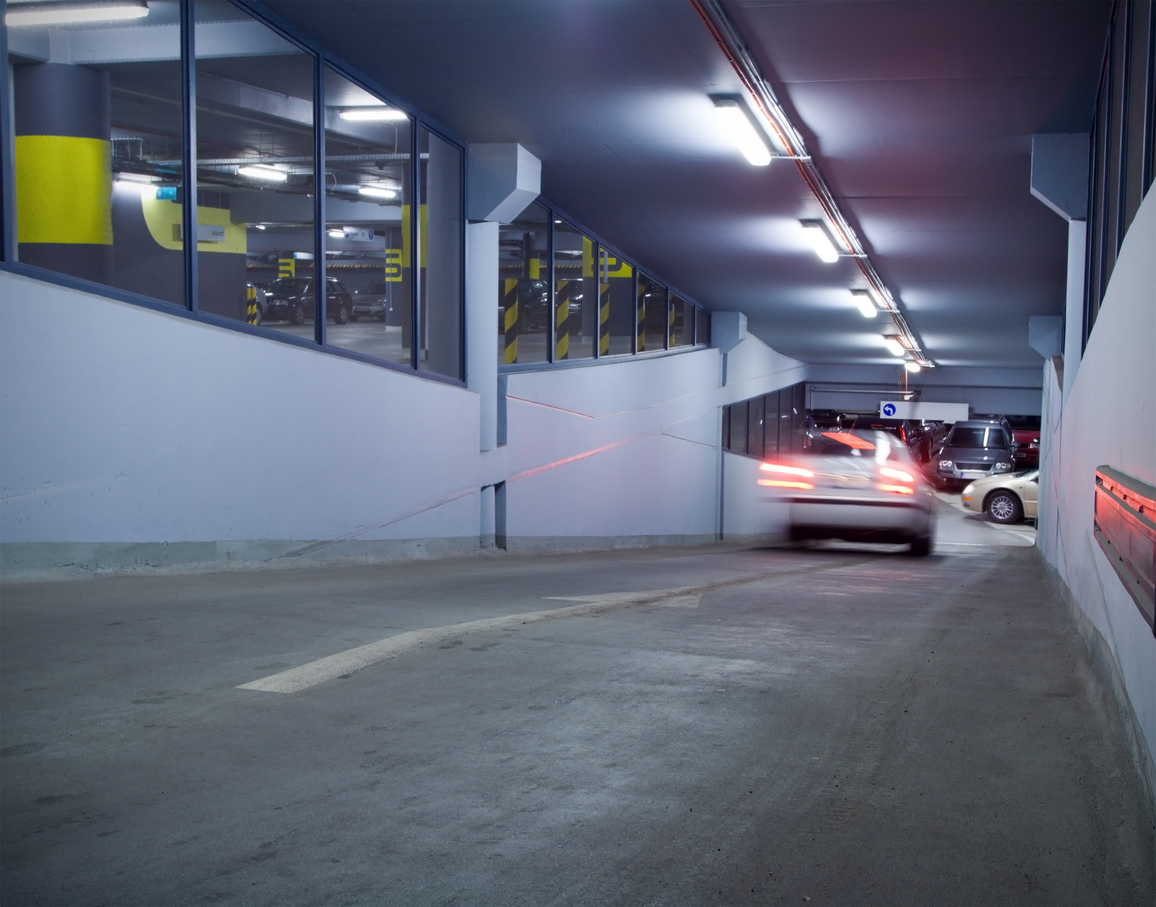 Traffic in underground parking garage with motion blur from moving car, car passing through parking garage